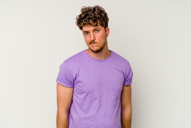 Jonge blanke man geïsoleerd op een witte achtergrond haalt schouders op en verward open ogen.