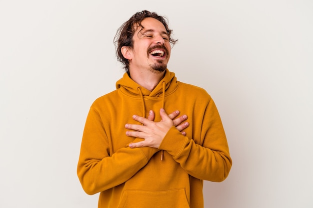 Jonge blanke man geïsoleerd op een witte achtergrond lachen handen op hart, concept van geluk te houden.
