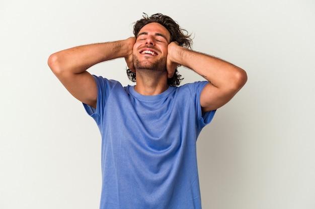 Jonge blanke man geïsoleerd op een witte achtergrond lacht vreugdevol handen op het hoofd te houden. geluk concept.