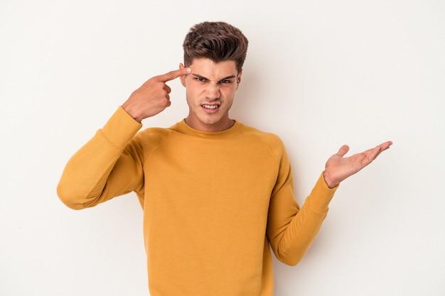 Jonge blanke man geïsoleerd op een witte achtergrond met een gebaar van teleurstelling met wijsvinger.