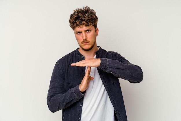 Jonge blanke man geïsoleerd op een witte achtergrond met een time-out gebaar.