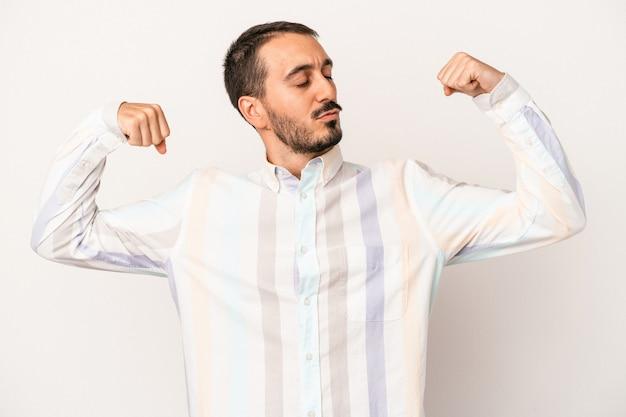 Jonge blanke man geïsoleerd op een witte achtergrond met kracht gebaar met armen, symbool van vrouwelijke kracht