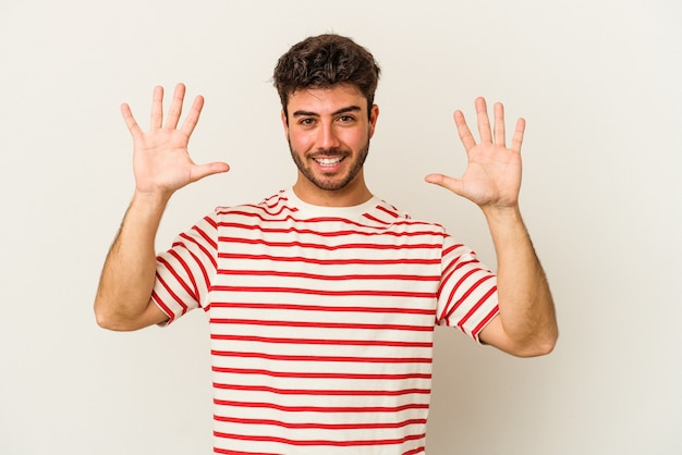Jonge blanke man geïsoleerd op een witte achtergrond met nummer tien met handen.