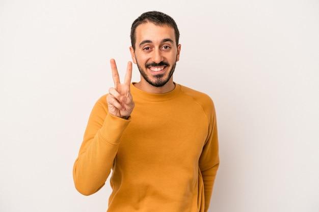 Jonge blanke man geïsoleerd op een witte achtergrond met nummer twee met vingers.