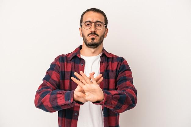 Jonge blanke man geïsoleerd op een witte achtergrond permanent met uitgestrekte hand weergegeven: stopbord, voorkomen dat u.