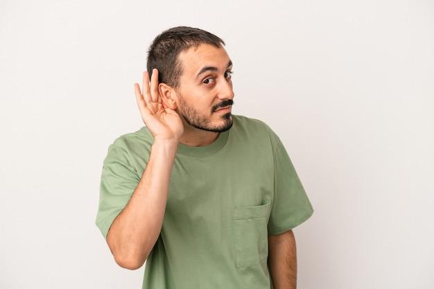 Jonge blanke man geïsoleerd op een witte achtergrond probeert te luisteren naar een roddel.