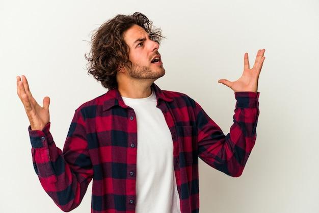 Jonge blanke man geïsoleerd op een witte achtergrond schreeuwen naar de hemel, opzoeken, gefrustreerd.