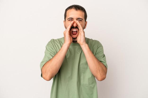 Jonge blanke man geïsoleerd op een witte achtergrond schreeuwen opgewonden naar voren.