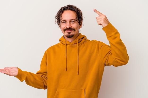 Jonge blanke man geïsoleerd op een witte achtergrond te houden en een product bij de hand te tonen.