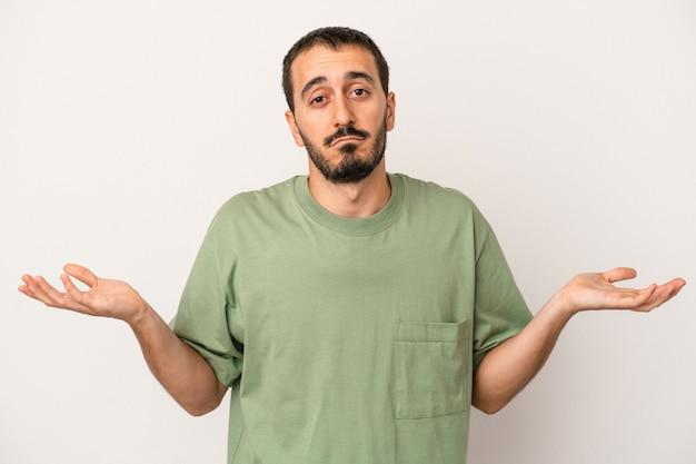 Jonge blanke man geïsoleerd op een witte achtergrond twijfelen en schouders ophalen in ondervraging gebaar.