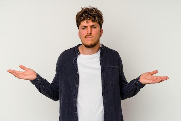 Jonge blanke man geïsoleerd op een witte achtergrond twijfelende en schouders ophalen in vragend gebaar.