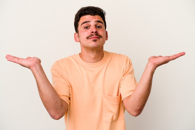 Jonge blanke man geïsoleerd op een witte achtergrond verward en twijfelachtig schouders ophalen om een kopie ruimte te houden.