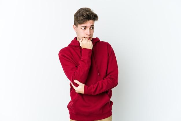 Jonge blanke man geïsoleerd op een witte achtergrond vingernagels bijten, nerveus en erg angstig.