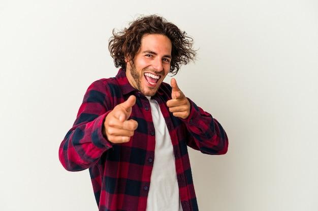 Jonge blanke man geïsoleerd op een witte achtergrond vrolijke glimlach wijst naar voren.