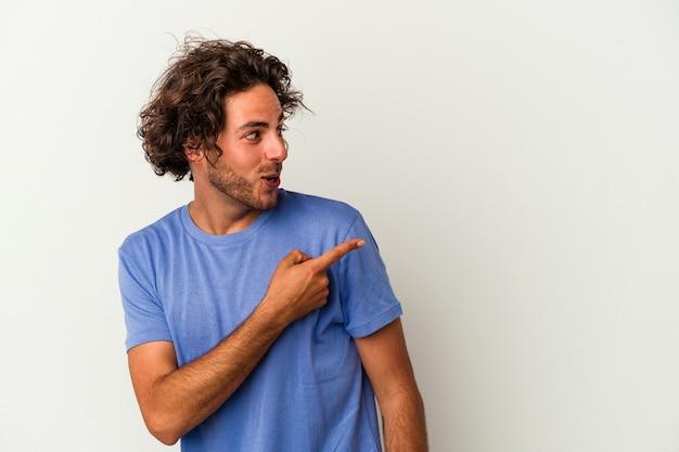 Jonge blanke man geïsoleerd op een witte achtergrond wijst met duim vinger weg, lachend en zorgeloos.