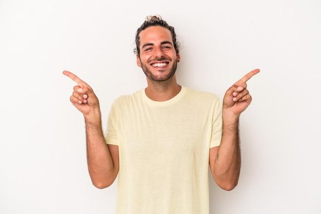 Jonge blanke man geïsoleerd op een witte achtergrond, wijzend naar verschillende kopieerruimten, een van hen kiezend, tonend met de vinger.