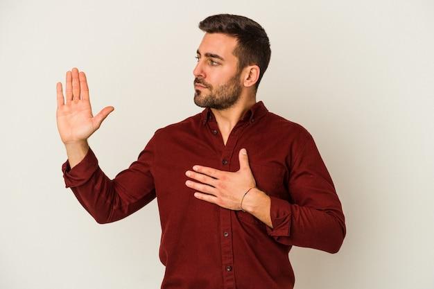 Jonge blanke man geïsoleerd op een witte muur een eed afleggen, hand op de borst leggen.