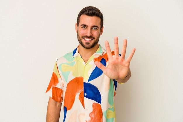 Jonge blanke man geïsoleerd op een witte muur glimlachend vrolijk tonend nummer vijf met vingers.