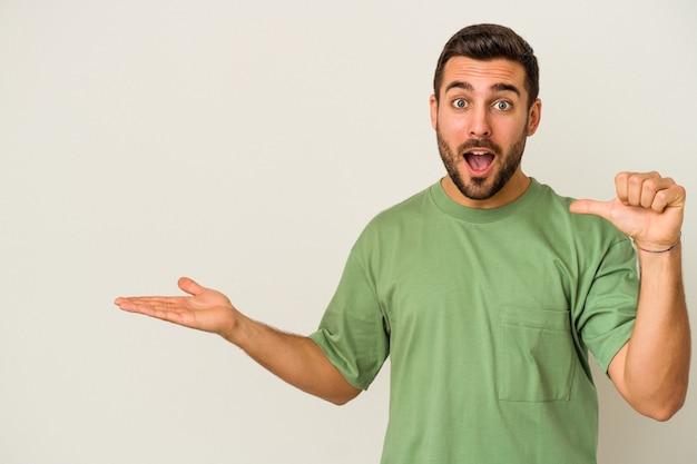Jonge blanke man geïsoleerd op een witte muur houdt kopie ruimte op een palm, hand over de wang houden