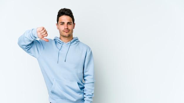 Jonge blanke man geïsoleerd op een witte muur met een afkeer gebaar, duimen naar beneden. meningsverschil concept.