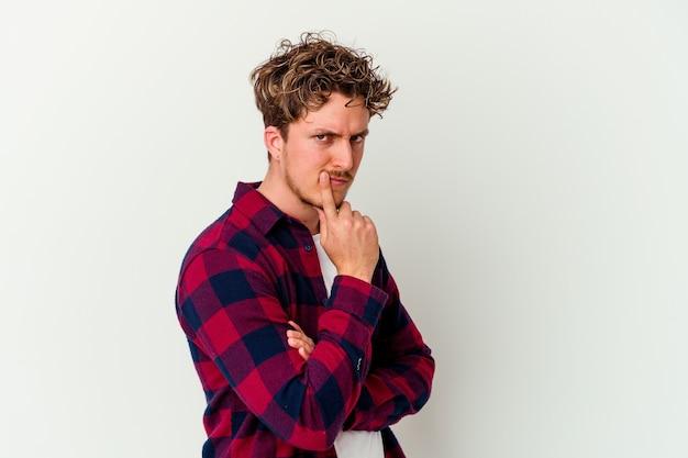 Jonge blanke man geïsoleerd op een witte muur ongelukkig te kijken naar de voorkant met een sarcastische uitdrukking