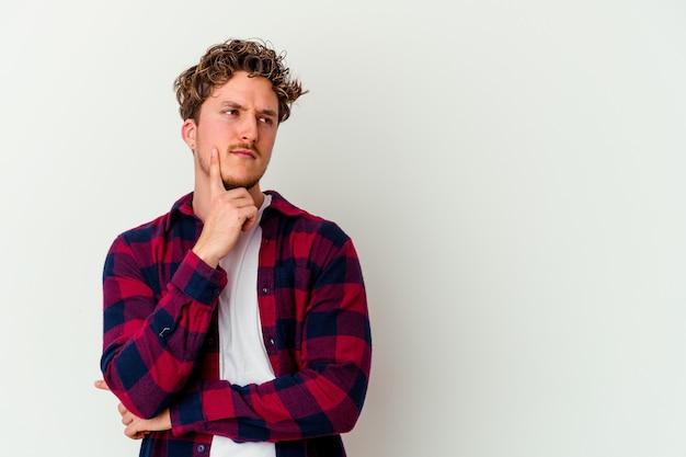 Jonge blanke man geïsoleerd op een witte muur opzij kijken met twijfelachtige en sceptische uitdrukking