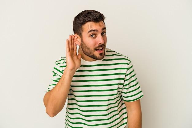 Jonge blanke man geïsoleerd op een witte muur proberen te luisteren een roddel.