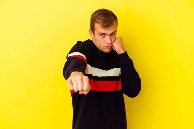 Jonge blanke man geïsoleerd op geel een klap, woede, vechten als gevolg van een argument, boksen.
