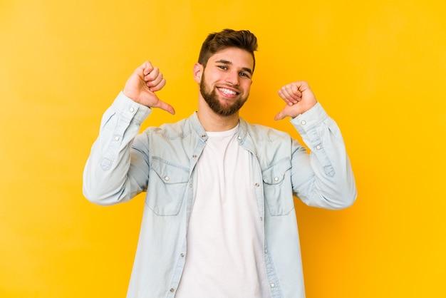 Jonge blanke man geïsoleerd op geel voelt zich trots en zelfverzekerd, voorbeeld om te volgen.