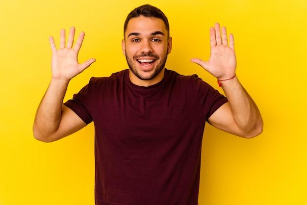 Jonge blanke man geïsoleerd op gele achtergrond die een aangename verrassing ontvangt, opgewonden en handen opsteekt.