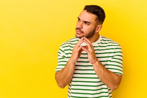 Jonge blanke man geïsoleerd op gele achtergrond die een plan in gedachten maakt, een idee opzet.