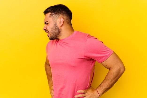 Jonge blanke man geïsoleerd op gele achtergrond die lijdt aan rugpijn.
