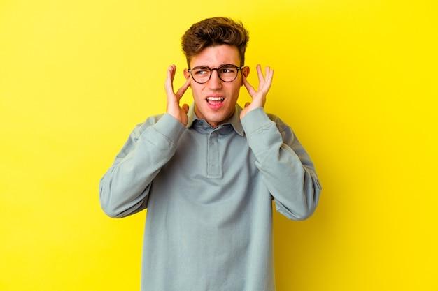 Jonge blanke man geïsoleerd op gele achtergrond die oren bedekt met vingers, gestrest en wanhopig door een luid ambient.