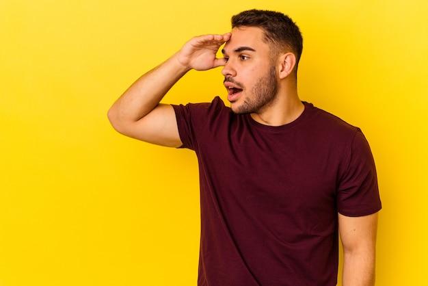 Jonge blanke man geïsoleerd op gele achtergrond die ver weg kijkt en hand op het voorhoofd houdt.