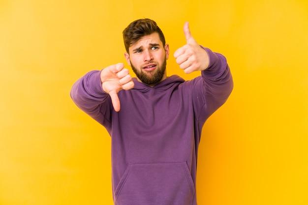 Jonge blanke man geïsoleerd op gele achtergrond duimen opdagen en duimen naar beneden, moeilijk kiezen concept