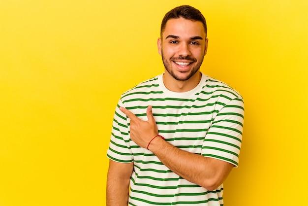 Jonge blanke man geïsoleerd op gele achtergrond glimlachend en opzij wijzend, iets tonend op lege ruimte.