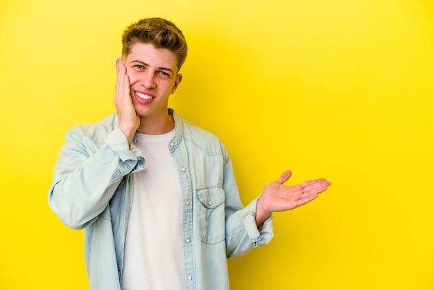 Jonge blanke man geïsoleerd op gele achtergrond houdt kopie ruimte op een palm, hand over de wang houden. verbaasd en opgetogen.