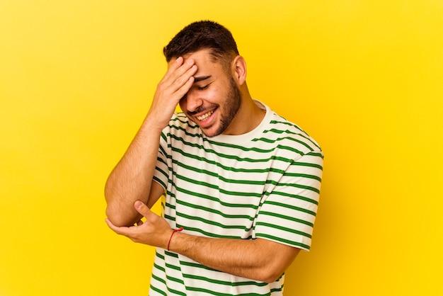 Jonge blanke man geïsoleerd op gele achtergrond knippert naar de camera door vingers, beschaamd bedekkend gezicht.