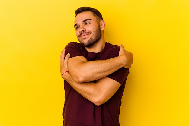Jonge blanke man geïsoleerd op gele achtergrond knuffels, zorgeloos en gelukkig lachend.