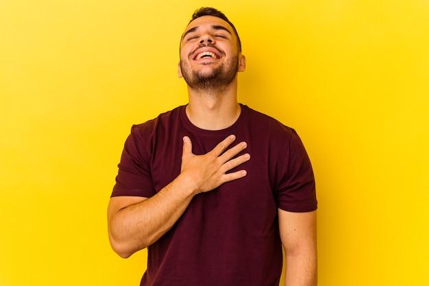 Jonge blanke man geïsoleerd op gele achtergrond lacht hardop terwijl hij de hand op de borst houdt.