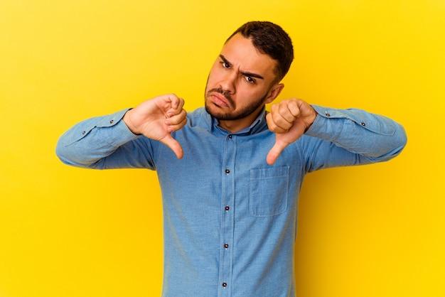 Jonge blanke man geïsoleerd op gele achtergrond met duim omlaag, teleurstelling concept.