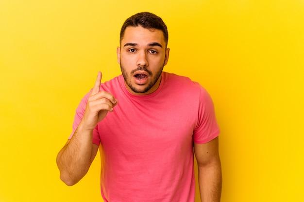 Jonge blanke man geïsoleerd op gele achtergrond met een idee, inspiratie concept.