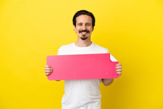 Jonge blanke man geïsoleerd op gele achtergrond met een leeg bordje