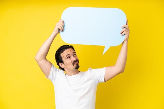Jonge blanke man geïsoleerd op gele achtergrond met een lege tekstballon en met droevige uitdrukking