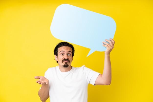 Jonge blanke man geïsoleerd op gele achtergrond met een lege tekstballon en twijfels