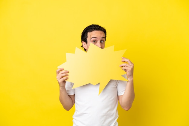 Jonge blanke man geïsoleerd op gele achtergrond met een lege tekstballon en zich erachter verschuilt