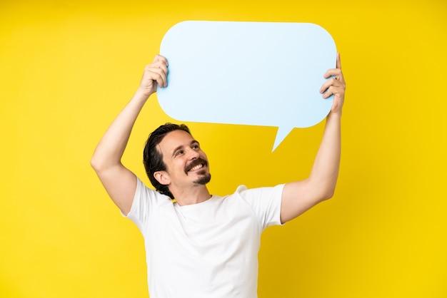 Jonge blanke man geïsoleerd op gele achtergrond met een lege tekstballon