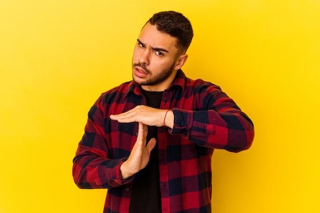 Jonge blanke man geïsoleerd op gele achtergrond met een time-out gebaar.