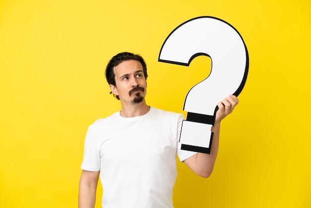 Jonge blanke man geïsoleerd op gele achtergrond met een vraagtekenpictogram en twijfels