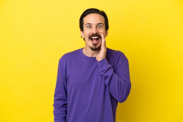 Jonge blanke man geïsoleerd op gele achtergrond met verrassing en geschokte gezichtsuitdrukking